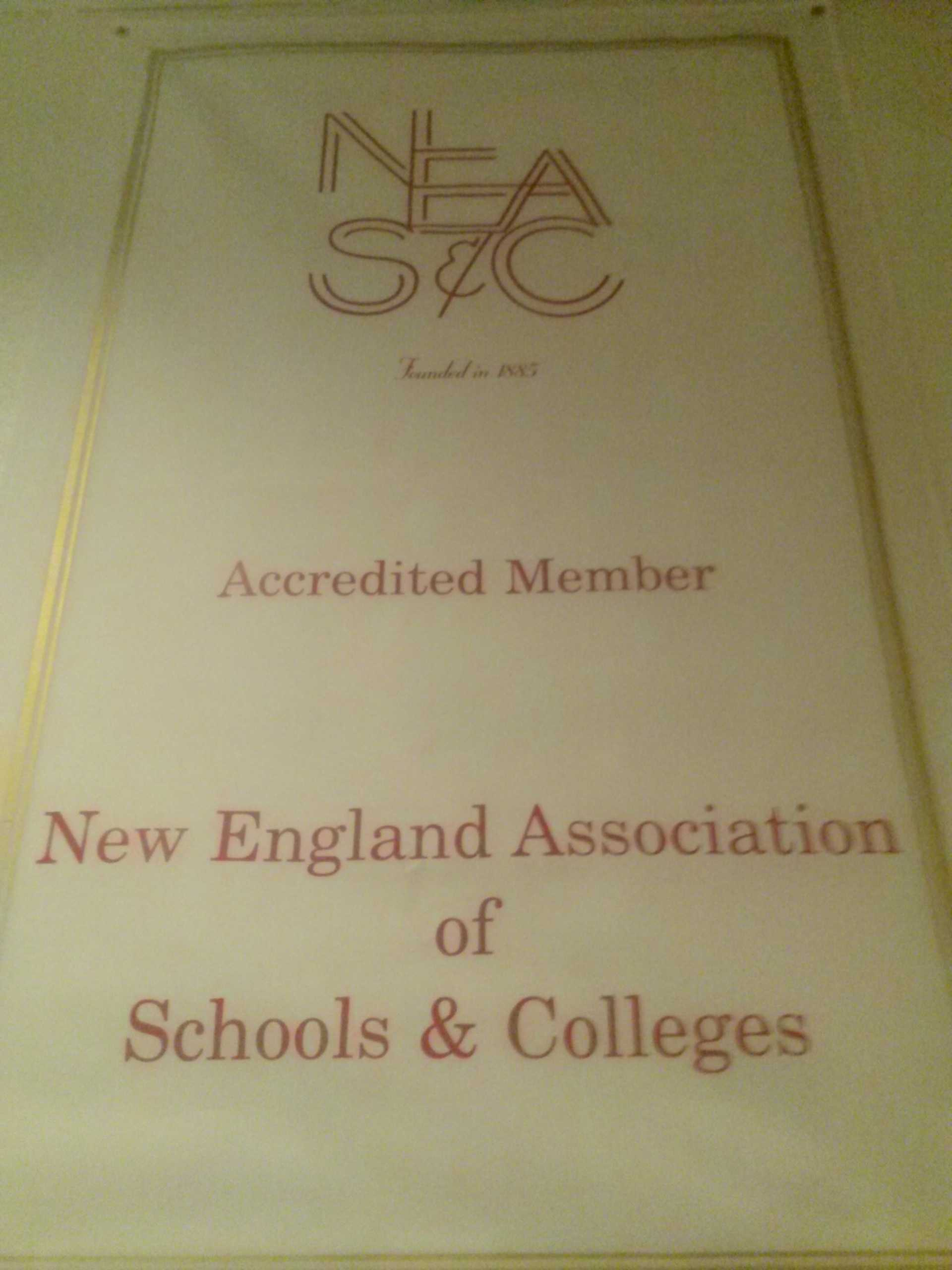 A front hall banner displays MacDuffie's NEASC accreditation, which is in the process of being renewed.