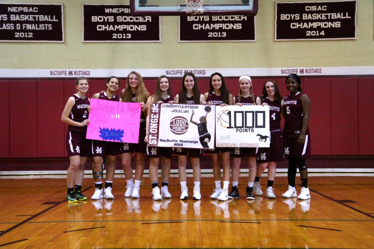 MacDuffie Girls Varsity Basketball team poses with senior Jocelyn St. Onge after she scored her thousandth point on January 6th, 2018. PC: Amy Cauley