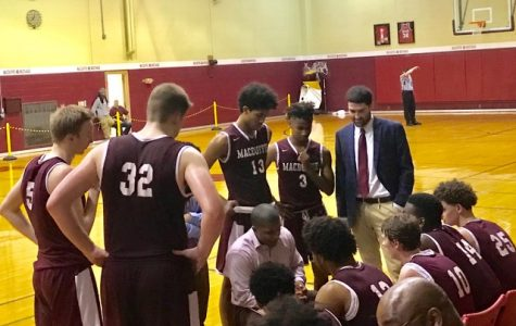 Coach Jacque Rivera discussing the game plan with the Boys' Prep Basketball Team. Photo by Sarah Hoffman.
