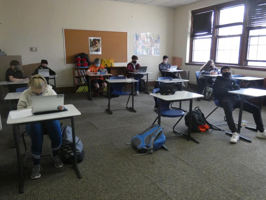 A British Literature class at MacDuffie in November 2020 taking precautions against the spread of COVID-19: face masks, distanced desks, and cracked windows for ventilation.